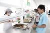 食堂工作人员在给学生打菜
